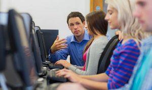 Profesor y alumnos en aula de formación empresarial